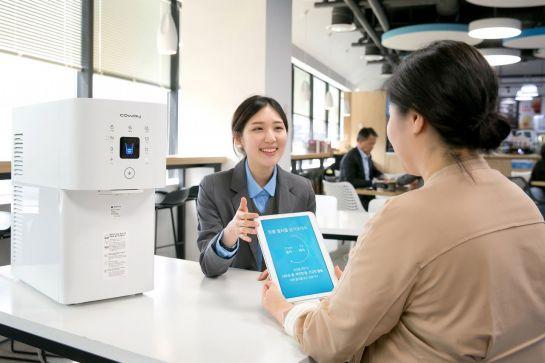 웅진코웨이 코디(왼쪽)가 고객에게 워터맵 서비스에 대해 설명하고 있다.