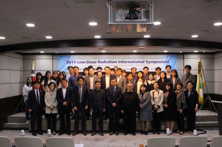 한국수력원자력 방사선보건원 저선량방사선 국제심포지엄에 참석한 박사 및 방사선보건 분야 국내외 인사와 산업부 연구과제 참여기관 연구진 등이 기념 촬영을 하고 있다.