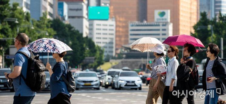 서울 한 낮 최고 기온이 30도를 웃돌며 여름 날씨를 나타낸 16일 서울 중구 태평로에서 시민들이 양산을 이용해 햇볕을 피하고 있다./강진형 기자aymsdream@