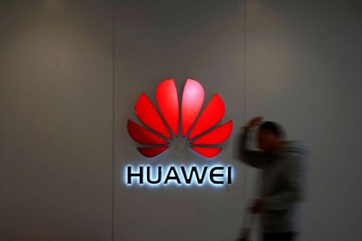 2018년 12월6일 한 남성이 중국 상하이 한 쇼핑몰 벽에 부착된 中 통신장비업체 화웨이의 로고 옆을 지나고 있다. (사진=연합뉴스)