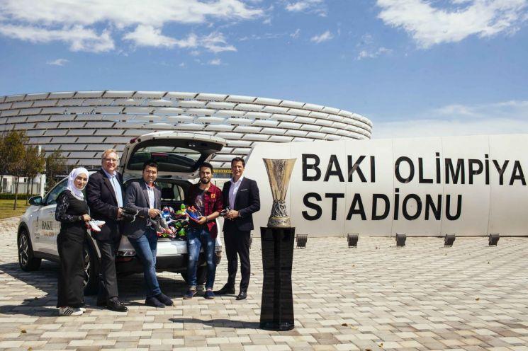 기아자동차가 UEFA 아동재단과 함께 요르단 자타리 난민 캠프의 어린이들을 위한 축구화 기부 캠페인을 진행한다. 기부 캠페인 주최자들과 포르투칼 전 국가대표 데쿠(왼쪽에서 세번째)가 아제르바이잔 바쿠의 올림픽 스타디움에서 기념 촬영을 하고 있다./ 사진=기아차