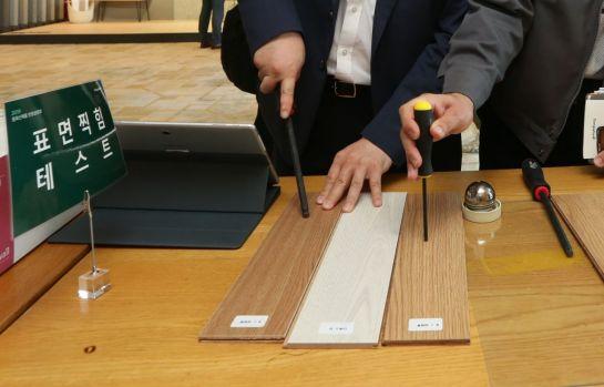 동화기업 신제품 론칭 행사 참가자들이 전시·체험 존에서 섬유판 강마루 '나투스진' 제품의 표면 찍힘 저항력을 테스트하고 있다.