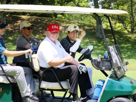 도널드 트럼프 미국 대통령과 아베 신조 일본 총리가 라운드 전 골프 카트에서 환하게 웃고 있는 모습.