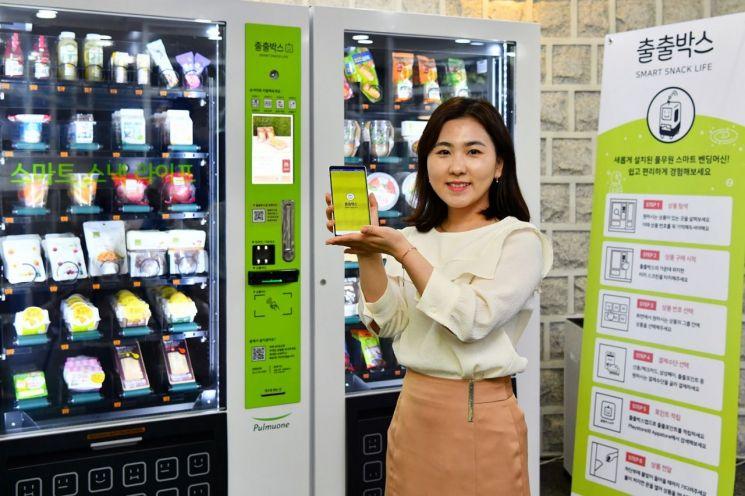 풀무원 직원이 스마트 자판기 '출출박스' 전용 모바일 앱을 선보이고 있다.