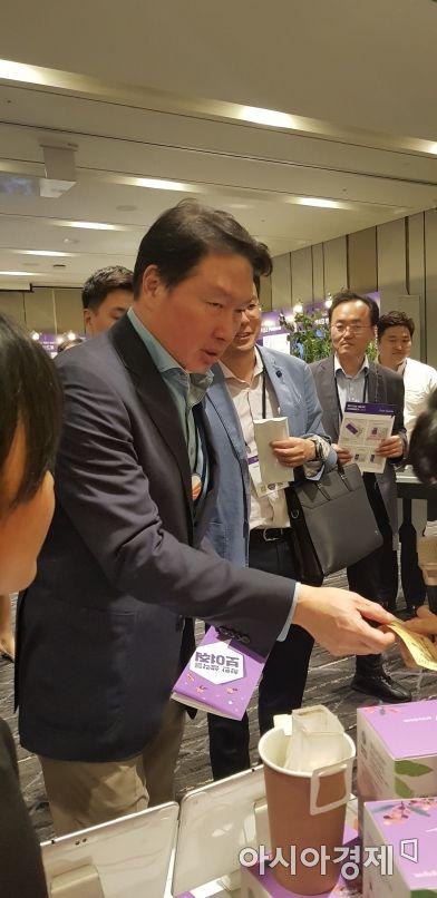▲ 최태원 SK그룹 회장이 28일 그랜드워커힐 호텔에서 열린 제 1회 'SOVAC 2019(Social Value Connect)' 행사에서 사회적기업 전시 부스를 찾아 설명을 듣고 물건을 구입하고 있다.