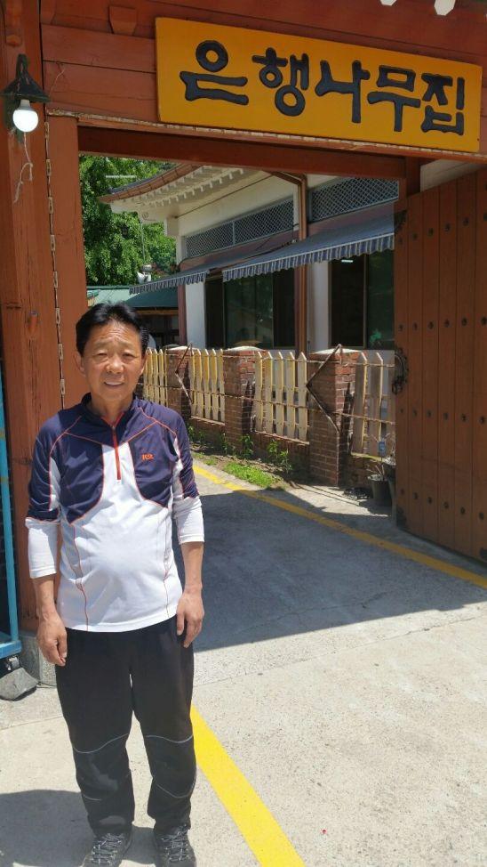 김영수 은행나무집 대표가 가게 앞에서 활짝 웃고 있다.