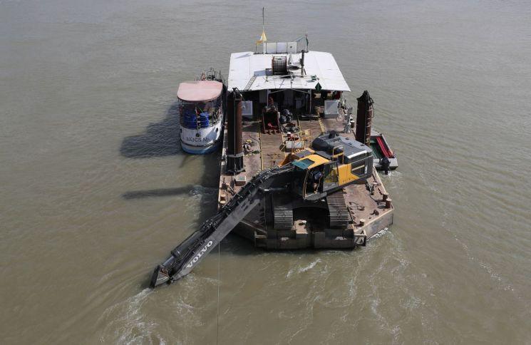 6일(현지시간) 다뉴브강 유람선 침몰사고 현장인 헝가리 부다페스트 다뉴브강 머르기트 다리 인근에 인양 준비작업에 투입될 포크레인이 소형 바지선 위에서 대기하고 있다.