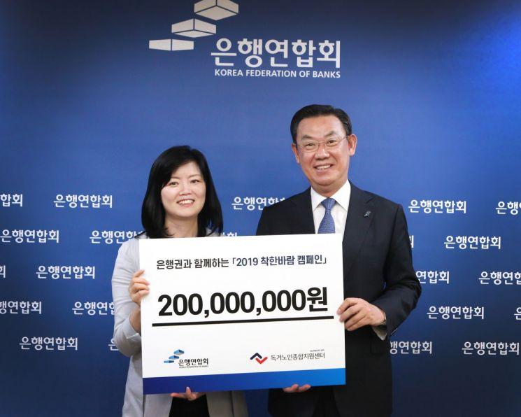 김태영 은행연합회장(오른쪽)이 지난 7일 김현미 독거노인종합지원센터장에게 '착한바람 캠페인' 후원금 2억원을 전달하며 기념촬영하고 있다.