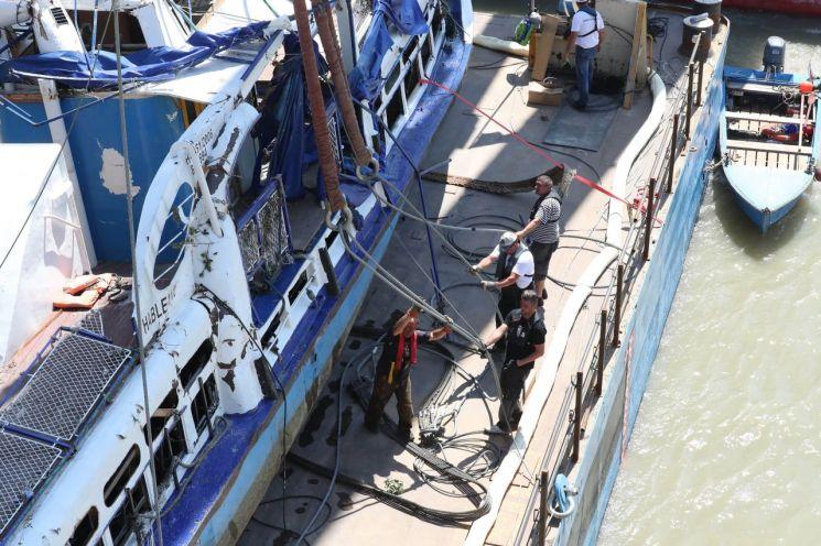 11일(현지시간) 헝가리 부다페스트 다뉴브강 머르기트 다리 아래에 정박한 바지선에서 관계자들이 허블레아니호 인야에 사용된 와이어를 정리하고 있다. <사진=연합뉴스>