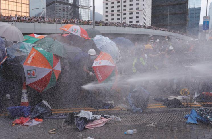 '범죄인 인도 법안'에 대한 홍콩 입법회(의회)의 심의가 예정된 12일, 이 법안에 반대하며 시위에 나선 시민들이 경찰이 쏜 물대포를 맞고 있다. (사진=연합뉴스)