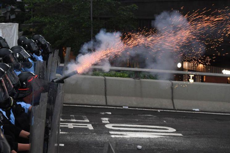 12일 홍콩 정부청사 건물 주변에서 경찰이 '범죄인 인도 법안'에 반대하는 시위대를 향해 최루탄을 발사하고 있다. (사진=연합뉴스)