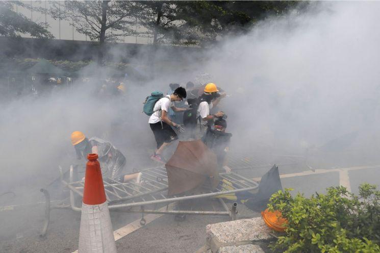 12일 홍콩 입법회(의회) 건물 주변에서 '범죄인 인도 법안'에 반대하는 시위대가 경찰이 발사한 최루가스를 피해 달아나고 있다. (사진=연합뉴스)