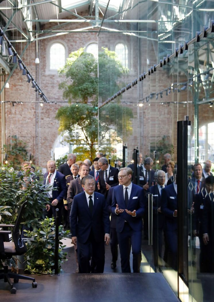 문재인 대통령이 15일 오전(현지시간) 스톡홀름 시내 노르휀 하우스에서 열린 '한-스웨덴 소셜 벤처와의 대화' 행사장에 입장하면서 에릭 엥겔라우-닐슨 노르휀 재단 CEO의 설명을 듣고 있다.  사진=연합뉴스