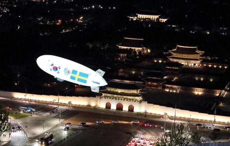 KT는 지난 14일 스웨덴 국빈 방문행사에서 5G 네트워크로 한국과 스웨덴을 연결해 광화문 상공에 떠있는 '5G 스카이십(skyship)'의 실시간 촬영 영상으로 한국의 야경을 감상하는 시연을 선보였다고 16일 밝혔다. 스웨덴 스톡홀름과 5G로 연결된  '5G 스카이십'이 서울 광화문 광장 상공을 비행하고 있다.