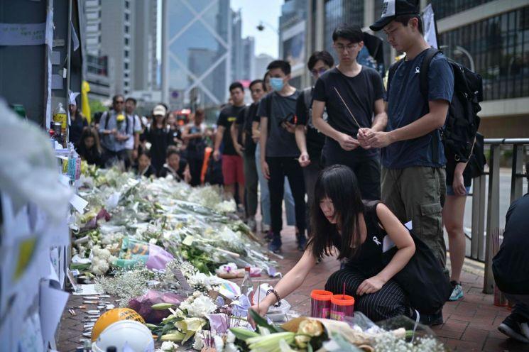 홍콩 도심 애드미럴티의 유명 쇼핑몰 퍼시픽 플레이스 4층 외벽에서 '범죄인 인도 법안'(일명 송환법)에 반대하는 고공농성을 벌이다 15일 오후 바닥으로 떨어져 숨진 30대 남성을 추모하기 위해 많은 시민들이 16일 추락 장소를 찾아 꽃다발을 놓고 명복을 빌고 있다. <사진=AFP연합>