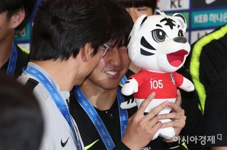국제축구연맹(FIFA) U-20 월드컵 준우승한 축구대표팀이 16일 인천국제공항을 통해 귀국했다. 이강인이 플래시 세례에 인형으로 얼굴을 가리고 있다./영종도=김현민 기자 kimhyun81@