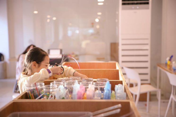 이문238 작업실에서 한 아이가 재료를 고르고 있다.[사진=리마크프레스]