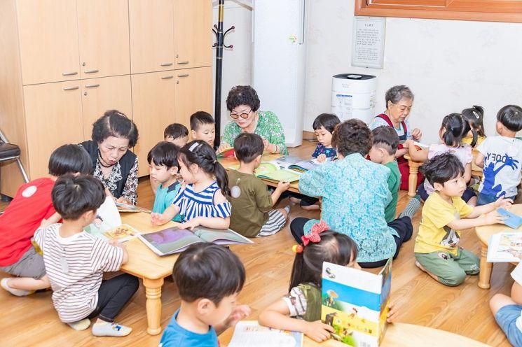 21일 광진구 중곡2동에 위치한 한마음경로당 어린이 북카페에서 어르신이 어린이들에게 동화책을 읽어주고 있는 모습