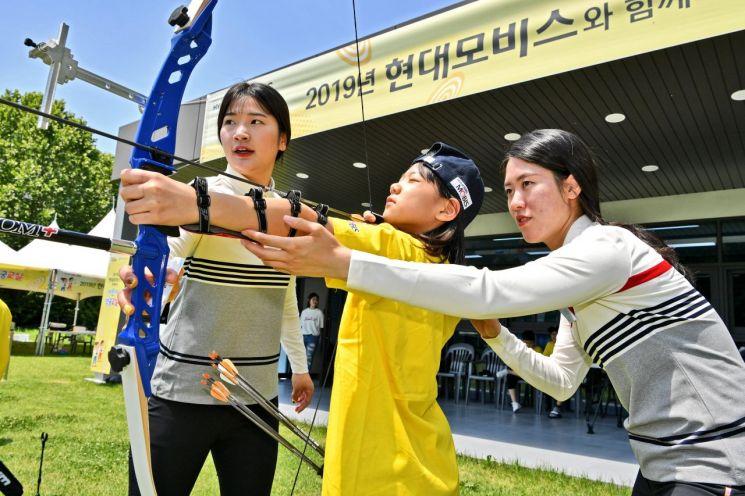 현대모비스가 22~23일 양일간 경기도 용인 현대모비스 양궁장에서 '어린이 양궁 교실'을 개최했다. 사진은 국가대표 강채영(왼쪽), 심예지(오른쪽) 선수가 초등학생에게 양궁을 지도하고 있는 모습/사진=현대모비스
