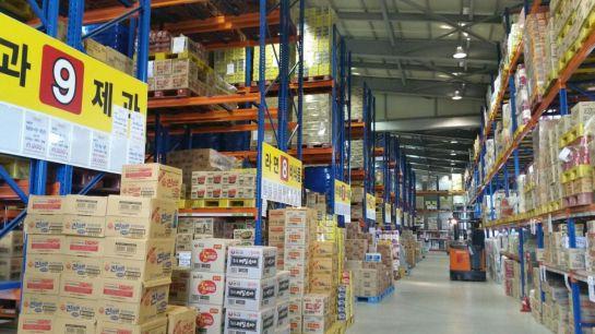 광주시수퍼마켓협동조합 중소유통공동구매물류센터에 공산품과 주류, 농산품 등을 담은 박스들이 천장 높이까지 가득 쌓여 있다.