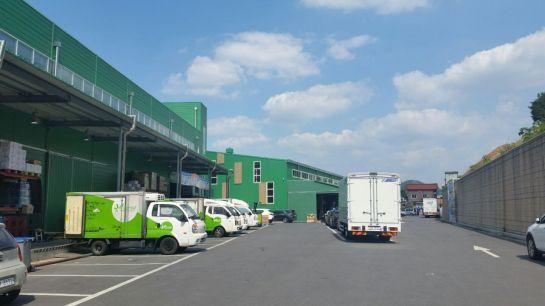 광주시수퍼마켓협동조합 중소유통공동구매물류센터 진입로와 주차장에 차량들이 가지런히 정차된 모습.