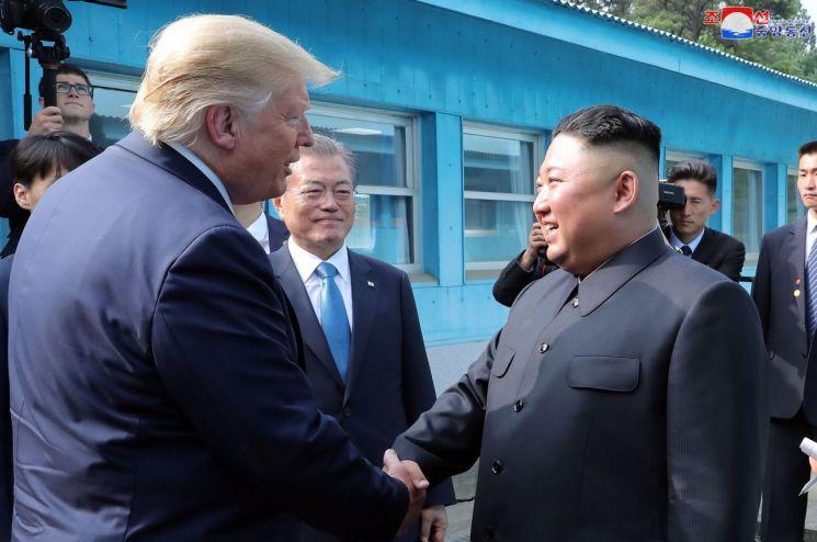 도널드 트럼프 미국 대통령과 김정은 북한 국무위원장이 30일 오후 판문점에서 악수하고 있다. 문재인 대통령이 이를 바라보고 있다.