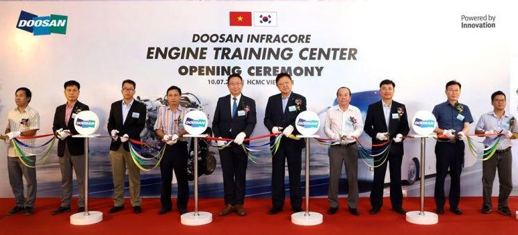 두산인프라코어가 지난 10일 베트남 호치민에서 엔진 트레이닝 센터 설립 기념 행사를 개최했다. 두산인프라코어 엔진BG 유준호 부사장(사진 왼쪽에서 다섯 번째)을 비롯해 베트남 딜러사와 버스 제조 및 운수 업체 대표자들이 센터 설립을 기념해 테이프 커팅을 하고 있다.