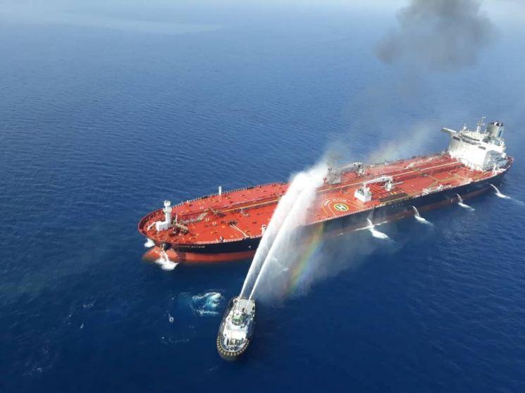 이란 해군 함정이 지난달 13일(현지시간) 오만해에서 공격을 받은 유조선에 접근해 진화 작업을 벌이고 있다. (사진=연합뉴스)