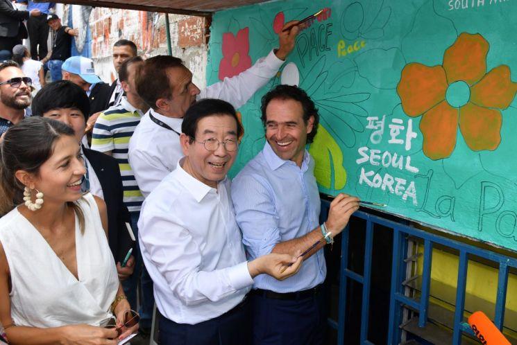 중남미를 순방 중인 박원순 시장은 11일(현지시간) 콜롬비아 메데인 '코뮤나 13'지역을 방문했다. 이 지역 주민과 예술가들이 박 시장을 환영하며 한글로 '평화'를 써달라고 요청해 '평화의 벽'에 '평화 SEOUL KOREA'란 메시지를 직접 쓰고 있다. 이날 페리코 구티에레즈 페데인 시장(오른쪽)도 현장을 찾아 박 시장과 평화의 메시지를 다시 한 번 함께 새겼다. (제공=서울시)