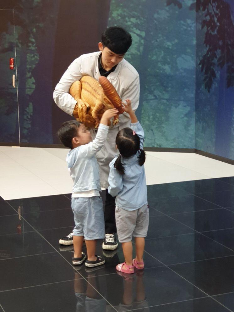어린이 관람객이 롯데백화점 김포공항점에서 열리고 있는 '쥬라기 월드 특별전'에서 공룡을 만져보고 있다.