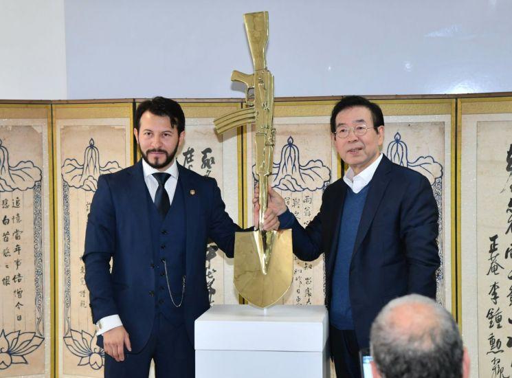 박원순 서울시장(오른쪽)이 콜롬비아 보고타 '세종학당'에서 알렉스 사스토케로부터 평화를 상징하는 자신의 작품 '변신(Metamorfosis)'을 전달하고 있다. (제공=서울시)
