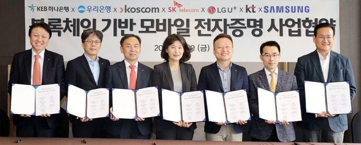 KEB하나은행, 우리은행, 코스콤으로 구성된 금융사들과 SK텔레콤, LG유플러스, KT로 구성된 통신 3사와 삼성전자는 사업협약식을 갖고 블록체인 기반의 모바일 전자증명 사업을 출범하기로 했다. 지난 12일 서울 중구 플라자호텔에서 개최된 협약식에서 7개 참여사 관계자들이 협약서를 들고 기념촬영을 하고 있다. 사진 왼쪽부터 하나은행 미래금융그룹 한준성 부행장, 우리은행 디지털금융그룹장 황원철 상무, 코스콤 미래성장본부 김계영 본부장, SK텔레콤 블록체인/인증 Unit장 오세현 전무, LG유플러스 FC부문장 이상민 전무, KT 블록체인비즈센터장 서영일 상무, 삼성전자 서비스기획그룹장 김주완 상무.