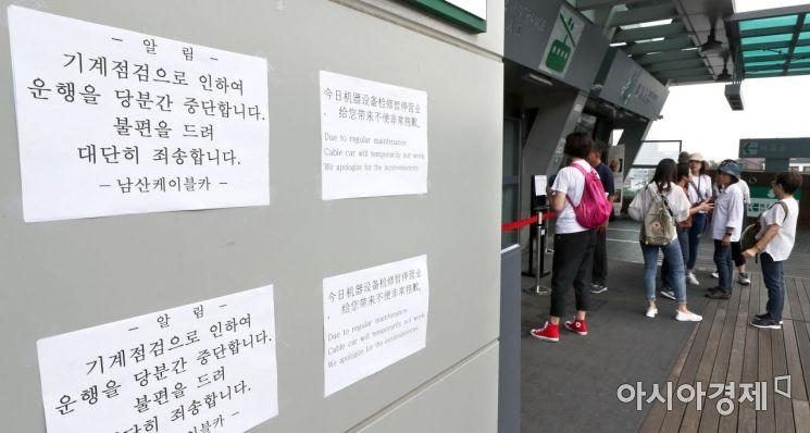 [포토] 남산 케이블카 운행중단 안내문 살펴보는 관광