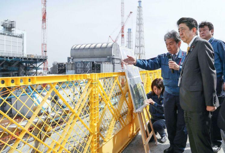 아베 신조(安倍晋三) 일본 총리가 지난 4월 후쿠시마(福島)현 오쿠마 소재 후쿠시마 제1원전을 방문해 관계자들의 설명을 듣고 있다. 과거와 달리 방호복이 아닌 양복 차림이다.<이미지출처:연합뉴스>