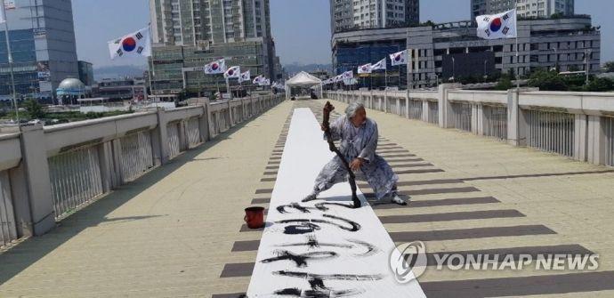 김동욱 서예가가 지난해 7월17일 울산교 위에서 제헌절 기념 서예 퍼포먼스를 펼치고 있다./사진=연합뉴스