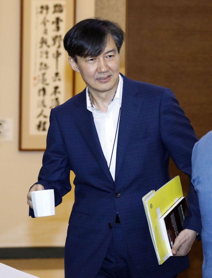 청와대 조국 민정수석이 22일 오후 청와대에서 열린 수석·보좌관회의에 입장하고 있다. 오른손에 회의자료와 함께 아오키 오사무의 책 '일본회의의 정체'를 들고 있다. [이미지출처=연합뉴스]