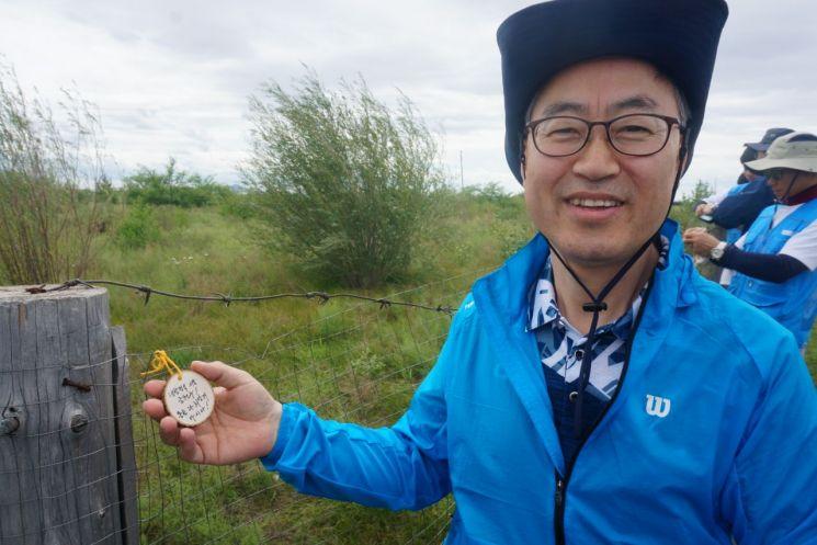지난 23일 국제자원활동을 위해 몽골을 방문한 유성훈 금천구청장이 몽골 바양노르솜 '금천희망의 숲' 울타리에 희망의 메시지를 달고 환하게 웃고 있다.