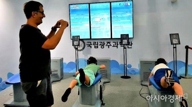 Stephane씨가 두 아이가 VR수영을 체험하는 것을 스마트폰으로 촬영하고 있다.