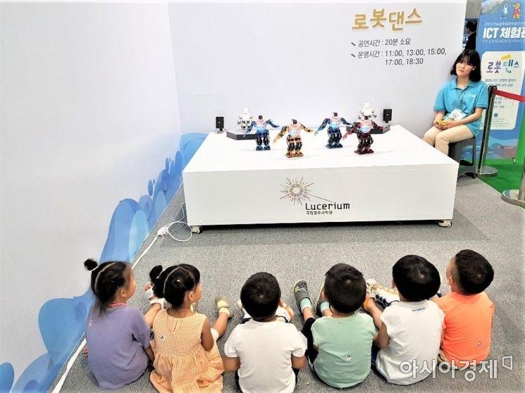 어린이들이 로봇들이 춤을 추는 것을 지켜보고 있다.