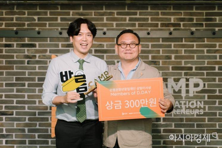 25일 은행권청년창업재단(디캠프)이 개최한 디데이에서 공동우승을 차지한 전성국 딕션 대표(왼쪽)가 김홍일 디캠프 상임이사와 기념촬영을 하고 있다.