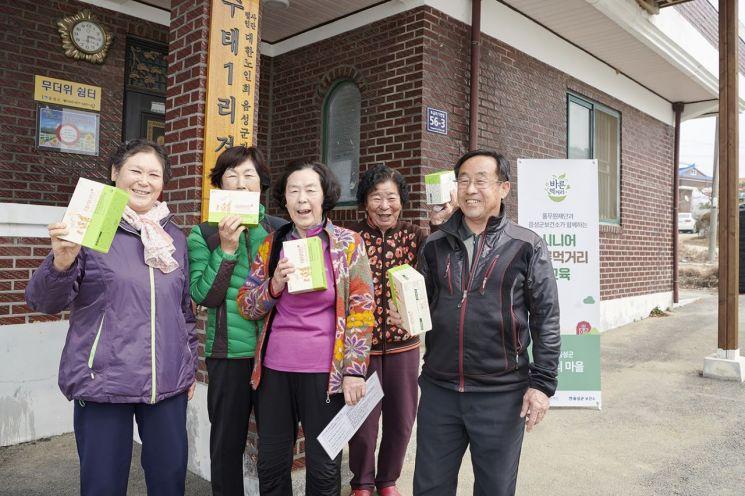 올 상반기 충북 음성군 수태리 마을에서 시행된 시니어 바른먹거리 교육에 참여한 어르신들이 풀무원이 제공한 건강기능식품을 들고 기념 사진을 촬영하고 있다.