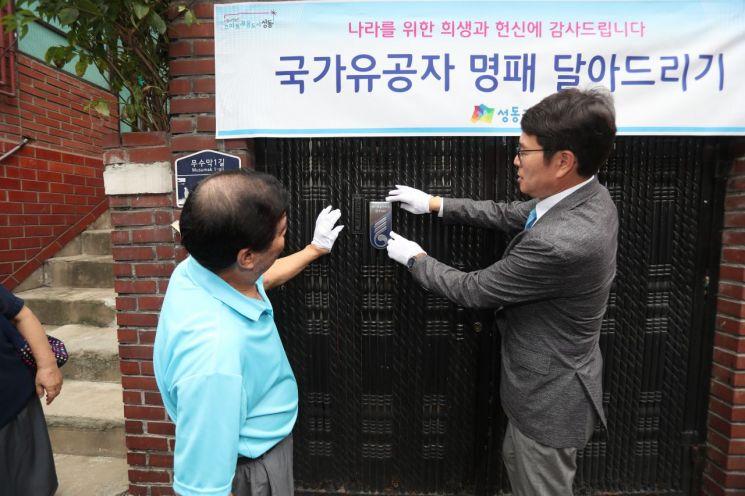 정원오 성동구청장(오른쪽)이 국가유공자 이재윤씨 집에 명패를 부착하고 있다