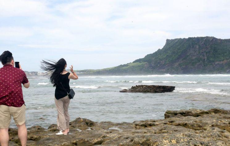 태풍 '레끼마'의 영향으로 강한 바람이 부는 10일 오후 제주 서귀포시 성산읍 광치기해변에서 관광객들이 높은 파도를 배경으로 사진을 찍고 있다. / 사진=연합뉴스