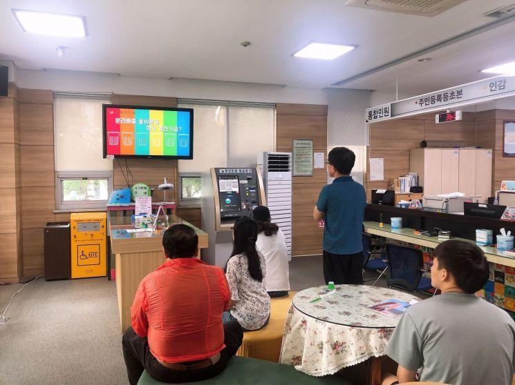 독산3동 주민센터 1층 민원실을 방문한 주민들이 홍보영상을 시청하고 있다.