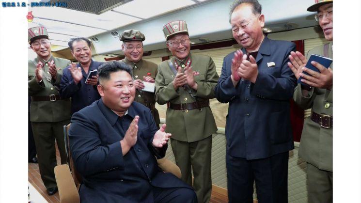 """북한 조선중앙TV가 11일 전날 함경남도 함흥 일대에서 실시한 2발의 단거리 발사체 발사 장면을 사진으로 공개했다. 북한 매체들은 김 위원장이 """"새로운 무기가 나오게 되었다고 못내 기뻐하시며 커다란 만족을 표시하시였다""""고 전했다. 사진은 김 위원장이 수행 간부들과 발사를 마친 뒤 박수를 치고 있는 것으로 보인다. [이미지출처=연합뉴스]"""