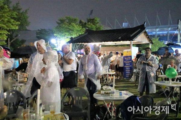 광주세계마스터즈수영대회 개막식이 열린 11일 오후 남부대학교 우정의 동산에 비가 내리는 것도 아랑곳 하지 않고 많은 시민들이 개막식을 즐기고 있다.