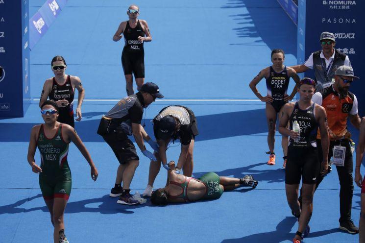 지난 8월 일본 도쿄 오다이바 마린파크에서 열린 도쿄 올림픽 트라이애슬론(철인3종) 테스트 이벤트에서 한 여성 참가 선수가 고온에 탈진해 쓰러져 있다.(사진=AP연합뉴스)