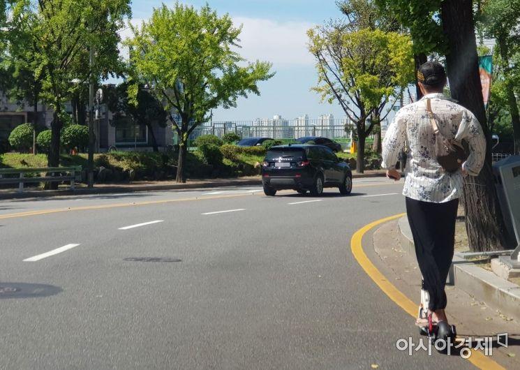 서울 남산 순환로에 아무런 보호장구를 착용하지 않은 한 시민이 전동킥보드를 타고 차들 사이를 질주하고 있다. /윤동주 기자 doso7@