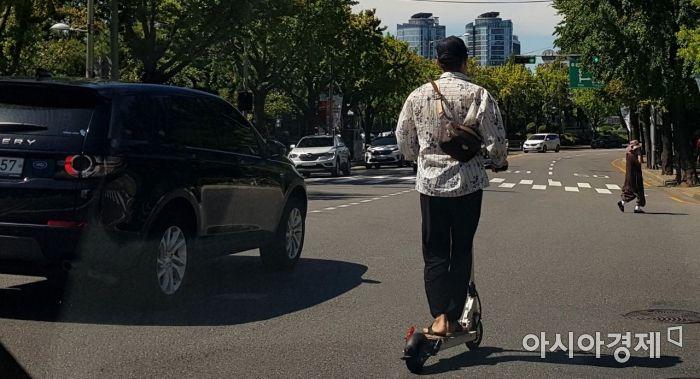 한 시민이 보호장구를 착용하지 않고 전동 킥보드를 타고 있다./윤동주 기자 doso7@