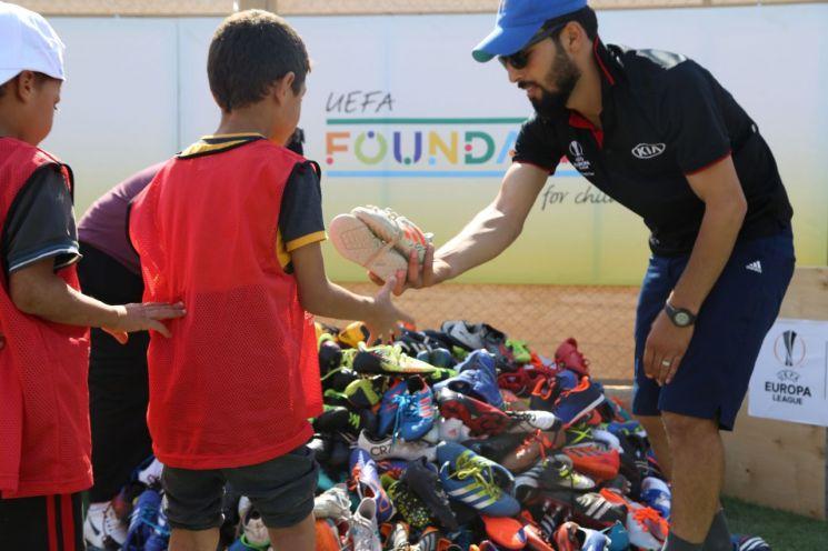 2018-19 시즌 UEFA 유로파리그 글로벌 트로피 투어를 통해 기부 받은 축구화를 관계자가 난민 어린이들에게 나눠주고 있는 모습.(사진=기아차)